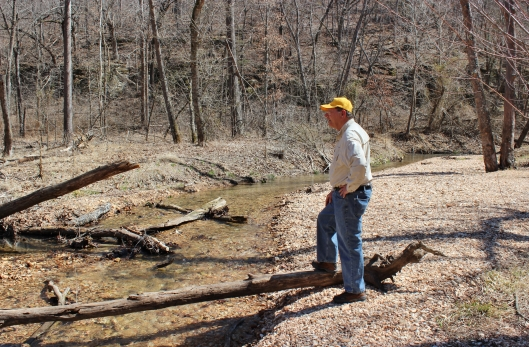 My husband Jim, looking across the creek toward Van Winkle Hollow and Beaver Lake.