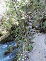 There is a trail that winds through the Big Spring Area, and at one point, goes behind the spring, and then leads up a rocky stairs to the trail atop a bluff.