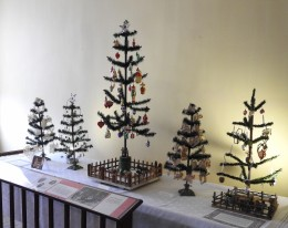 This display of feather trees is decorated with ornaments indicative of different eras in Hermann's Christmas traditions. The first tree on the left has scherenschnitte ornaments that were cut in the 1940's.
